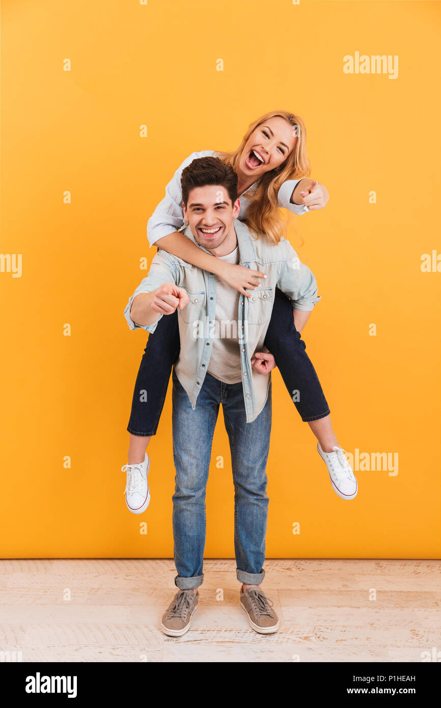 Full length photo of smiling couple having fun and pointing fingers at you while man piggybacking happy woman isolated over yellow background - Stock Image