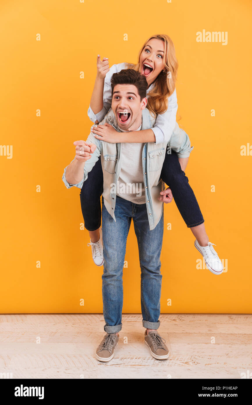 Full length image of caucasian couple having fun and pointing fingers at copyspace while man piggybacking joyful woman isolated over yellow background - Stock Image