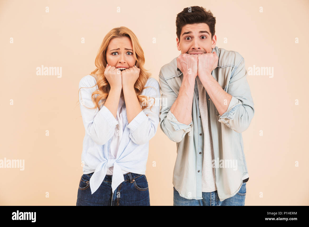 Image of stressed people man and woman in basic clothing expressing fright and biting their fists isolated over beige background - Stock Image
