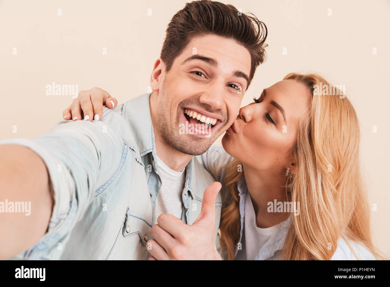 Portrait of happy man taking selfie photo and gesturing thumb up at camera while adorable woman kissing his cheek isolated over yellow background - Stock Image