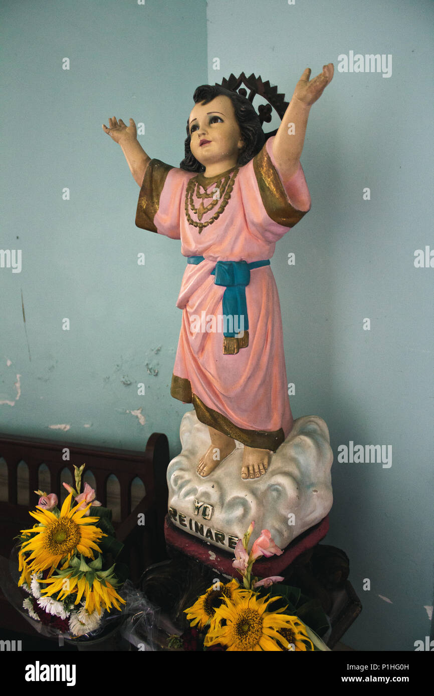 A small Jesus statue dressed in pink that some would regard as Kitsch - Stock Image
