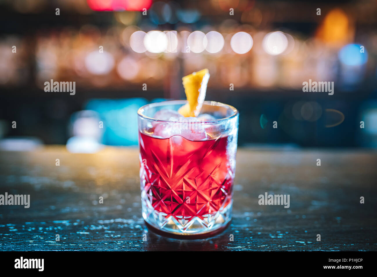 Pink and red Fresh colorful exotic alcoholic cocktail with lemon and ice in the bar. Colorful pink Soft drink with ice on the bar desk Colorful Mojito - Stock Image