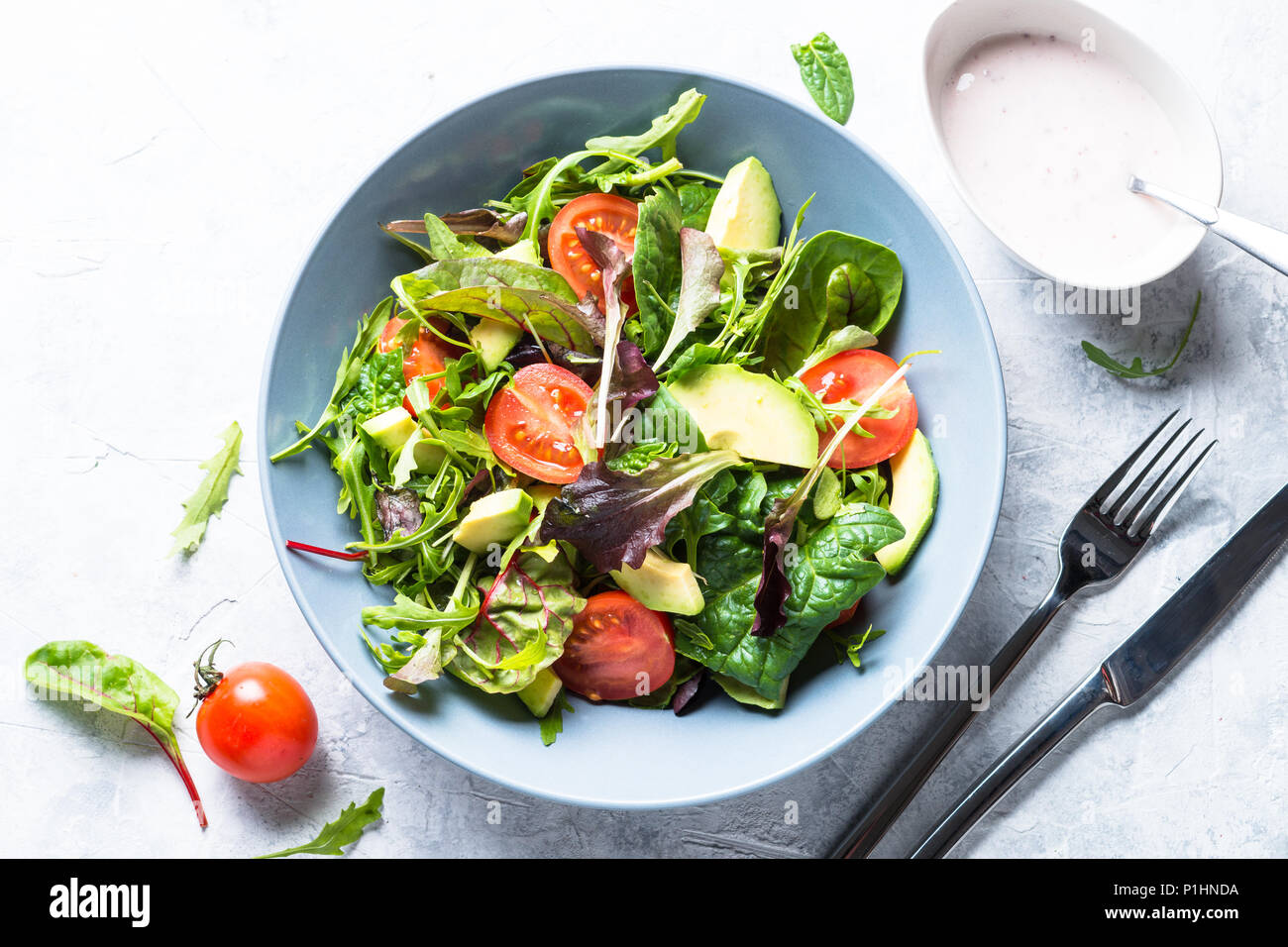 Fresh green salad with mixed green leaves, tomatoes and avocado with yogurt sauce. Clean eating and diet food. - Stock Image