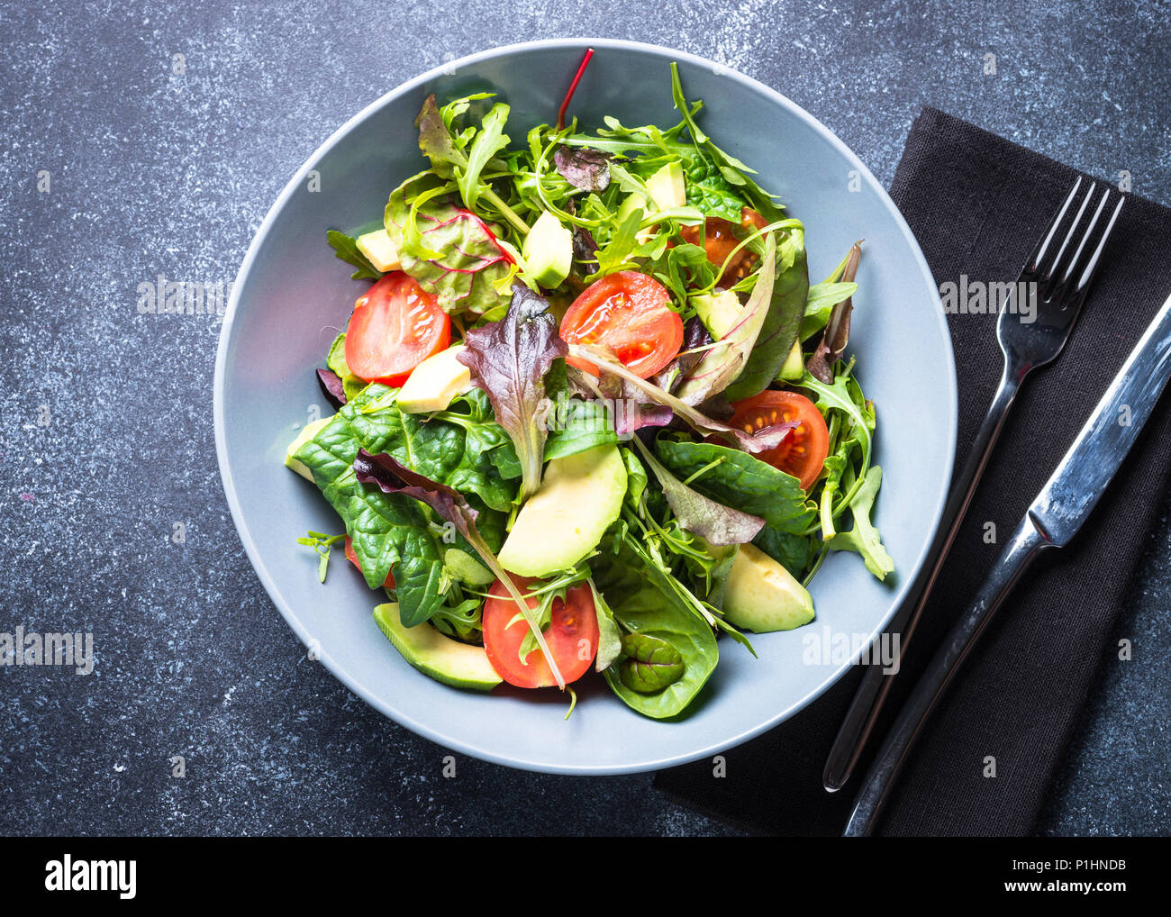 Fresh green salad with mixed green leaves, tomatoes and avocado on dark stone table. Clean eating and diet food. Top view. Stock Photo