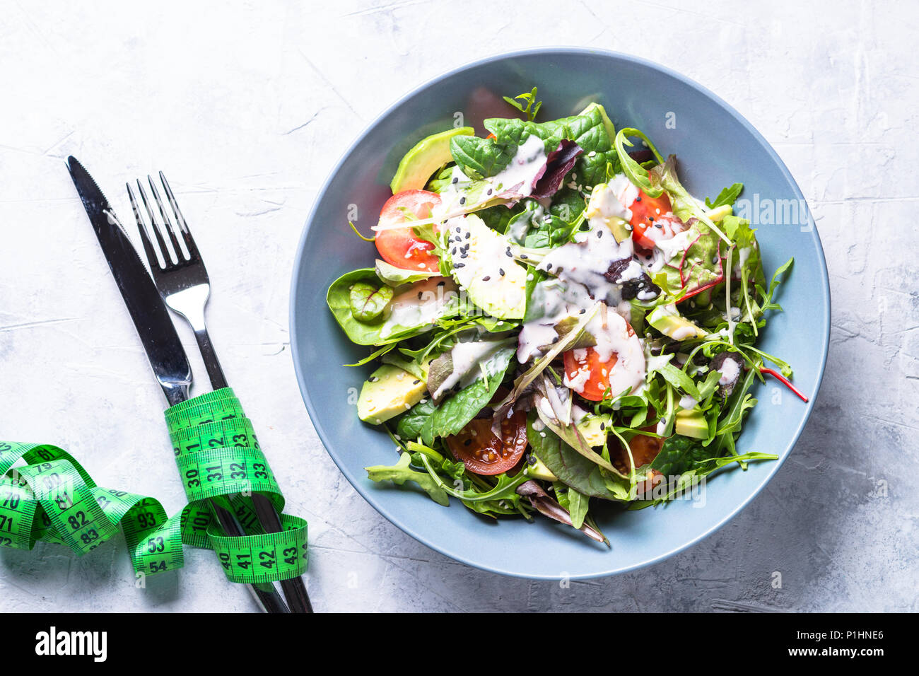 Fresh green salad with mixed green leaves, tomatoes and avocado with yogurt sauce and sesame. Low-calorie and weight less food. - Stock Image