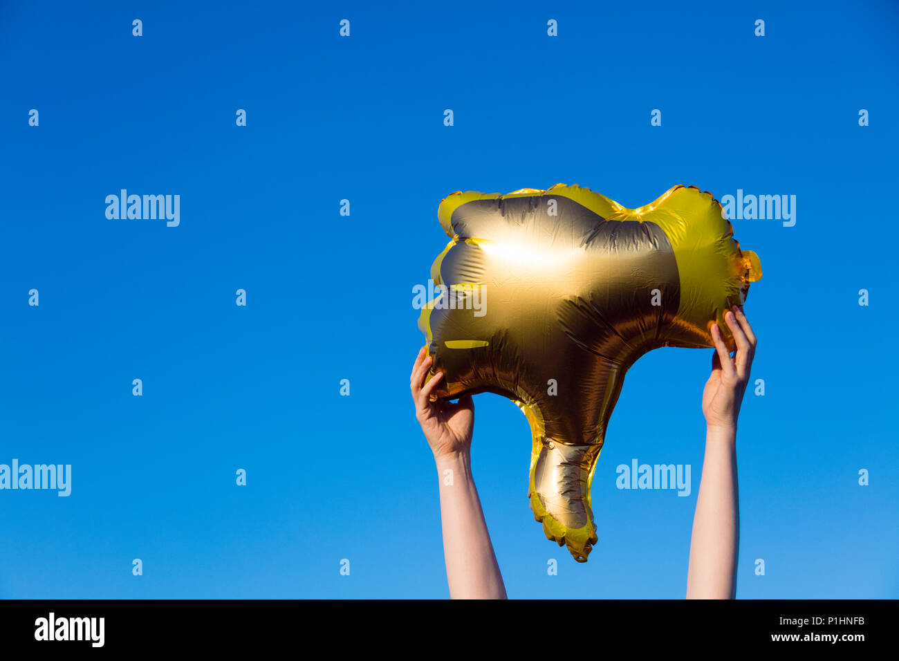 Golden thumbs down dislike balloon held up against a bright blue summer sky - Stock Image
