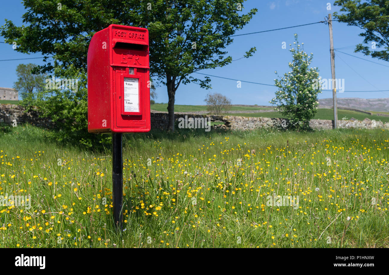 Red post box in a rural situation, North Yorkshire, UK. - Stock Image