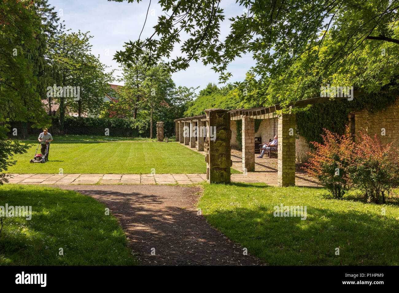 A gardener mows the lawn in Malmesbury Abbey gardens, while a visitor sits in the sunshine and rests, Wiltshire UK - Stock Image