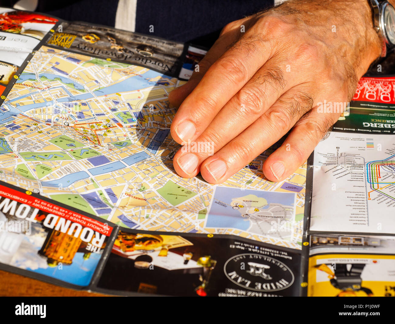 A man's hand resting on top of a  travel map. - Stock Image