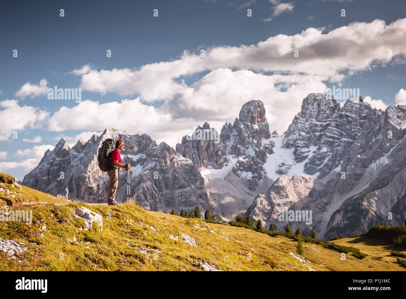 hiker in front of Alps mountains - Stock Image