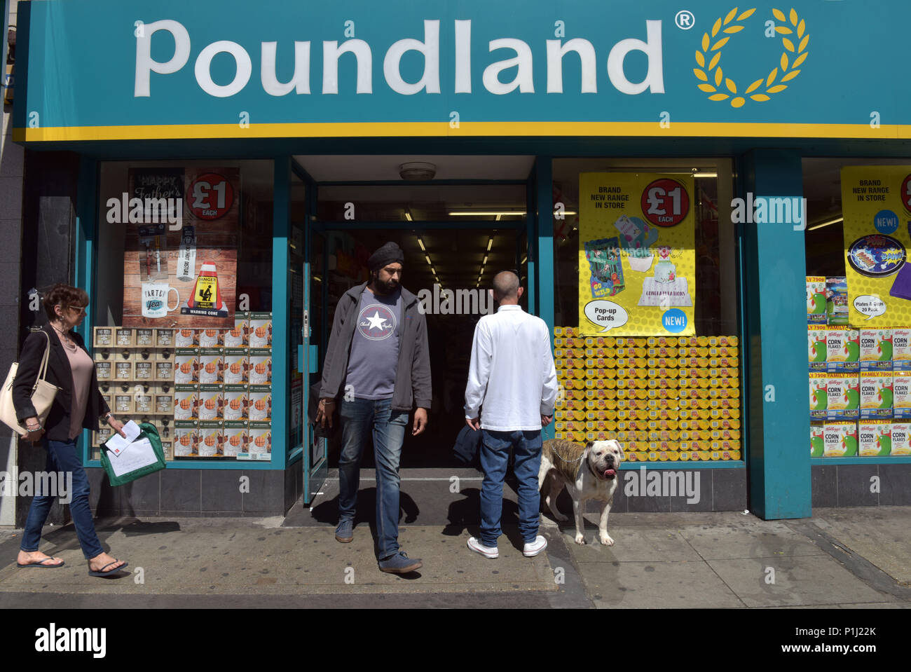 People and shoppers walk past the discount store Poundland on Camden High Street in North London. Poundland has done well during austerity. - Stock Image