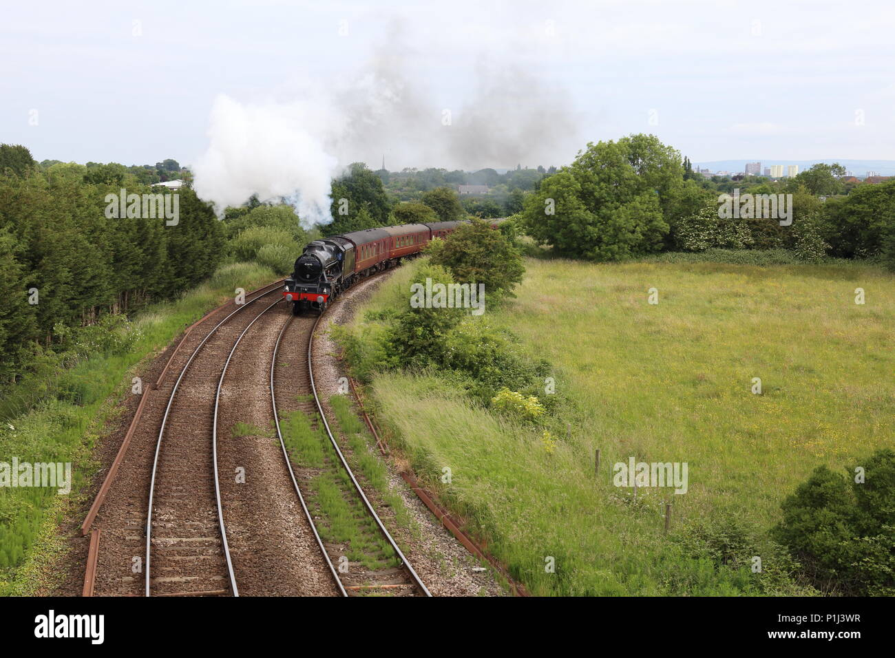 The Fellsman Steam Locomotive leads its carriages around the Farington Curve on its trip up the Settle Carlisle railway trough Lancashire countryside. - Stock Image