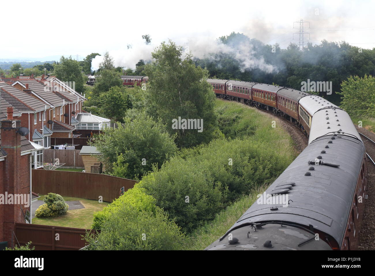 The Fellsman Steam Locomotive leads its carriages around the Farington Curve on its trip up the Settle Carlisle railway past private homes and gardens - Stock Image