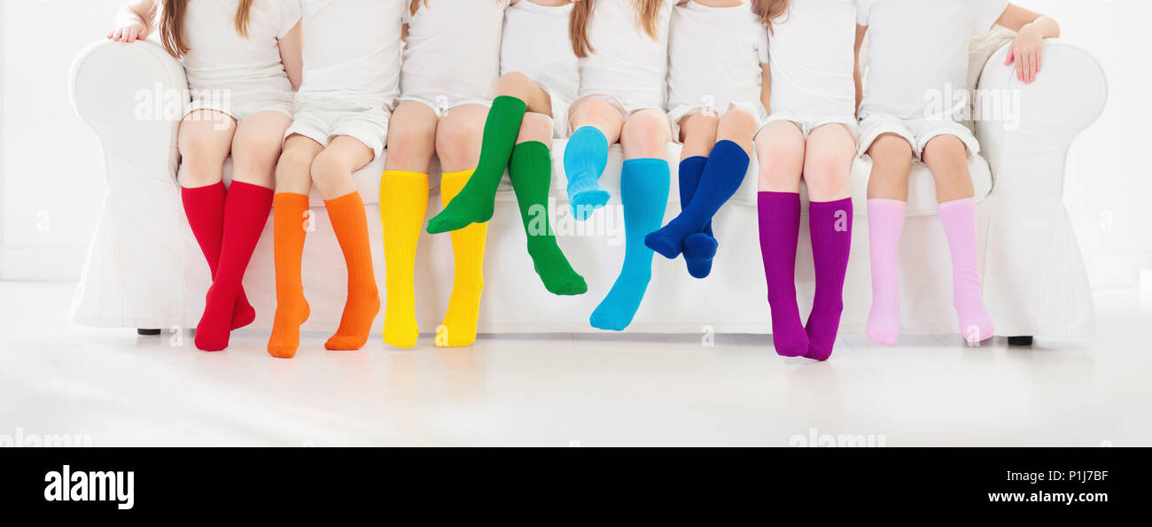 9323537d739 Kids wearing colorful rainbow socks. Children footwear collection. Variety  of knitted knee high socks and tights. Child clothing and apparel. Kid fash