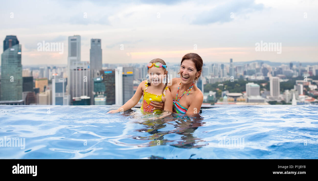Children swimming in roof top outdoor pool on family vacation in Singapore. City skyline from infinity pool in luxury hotel. Kids swim and enjoy skysc - Stock Image