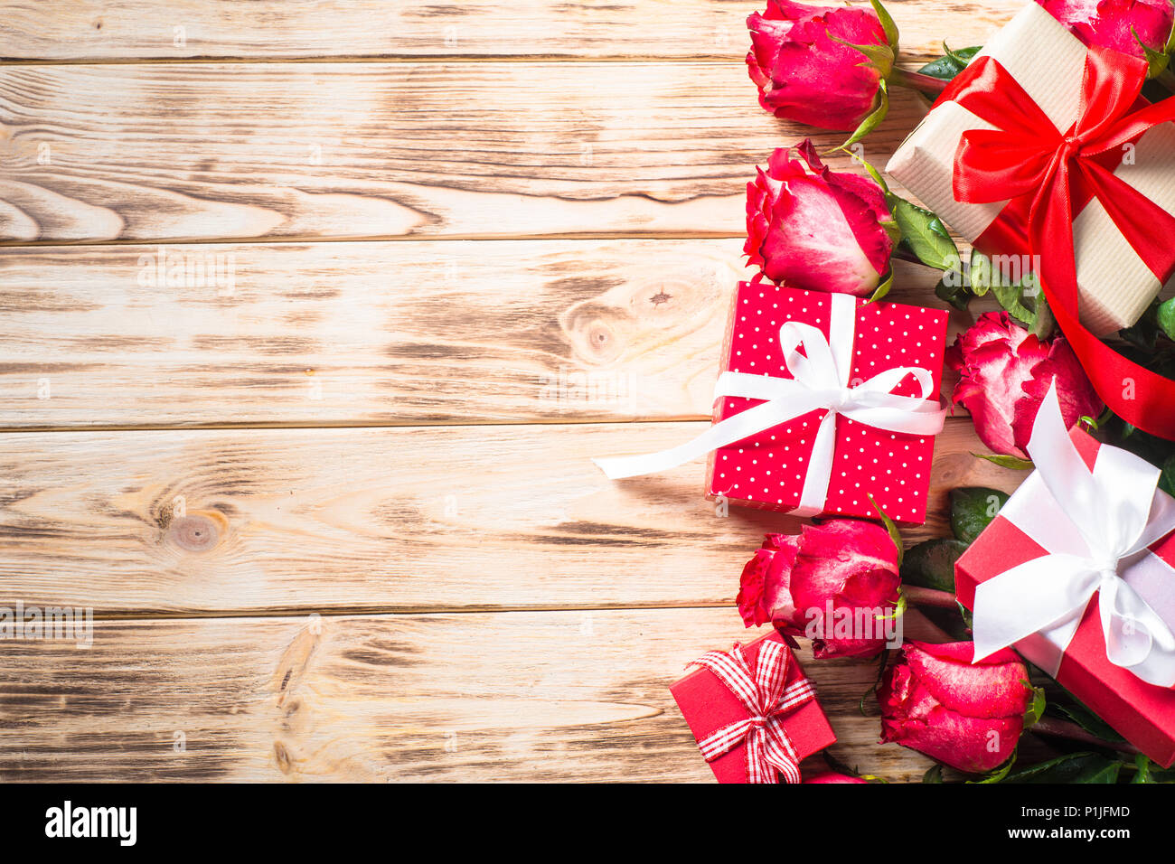 Red rose flower and present box on wooden table. Top view with copy space. Holiday background. - Stock Image