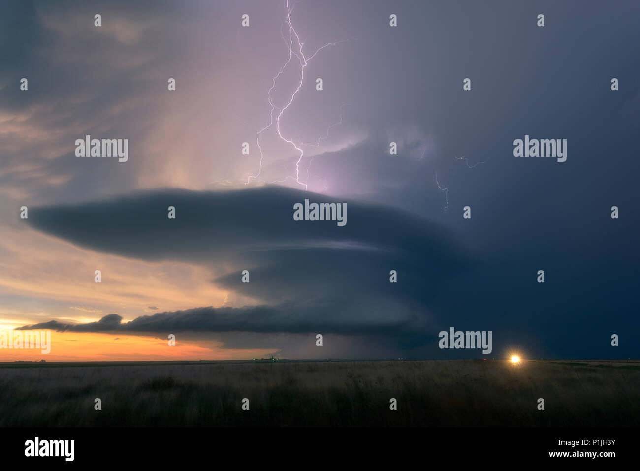 Cloud-to-cloud lightning during sunset with a supercell over the fields of Leoti, Wichita County, Kansas, USA on May 21st 2016 - Stock Image