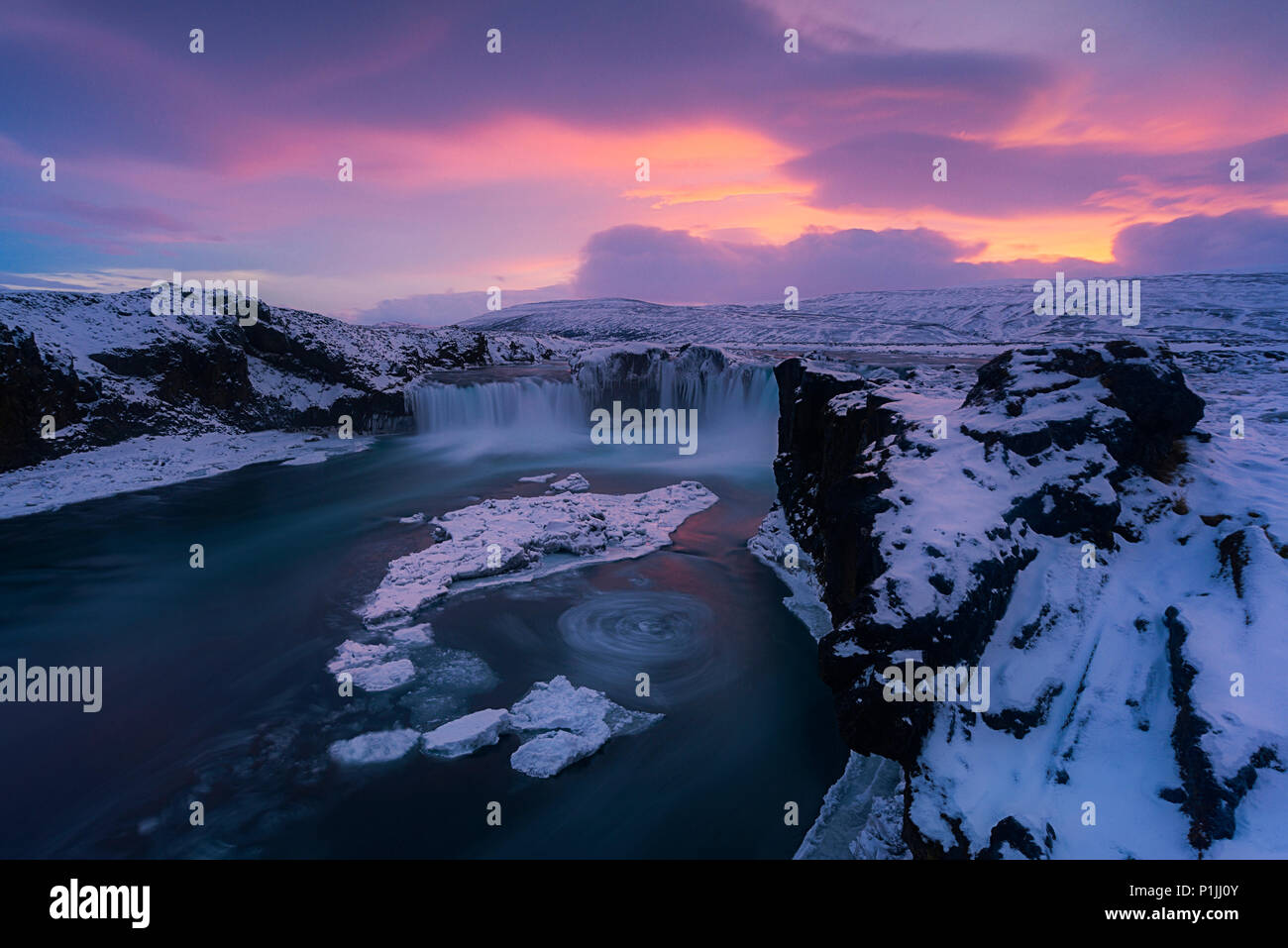 Sunset over Godafoss waterfall at ice and snow in winter, highlands, Iceland - Stock Image