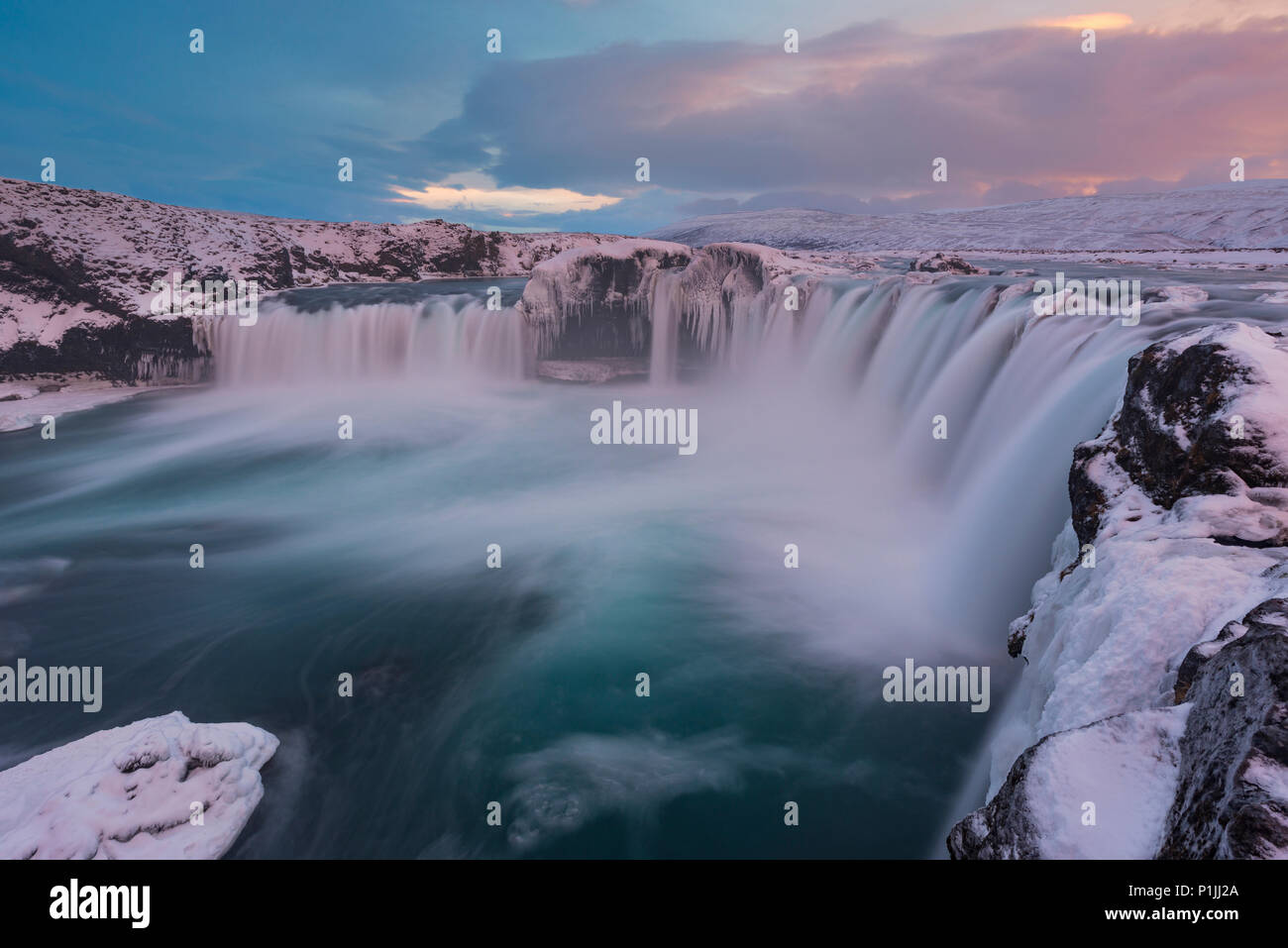 Evening light over Godafoss waterfall at ice and snow in winter, highlands, Iceland - Stock Image