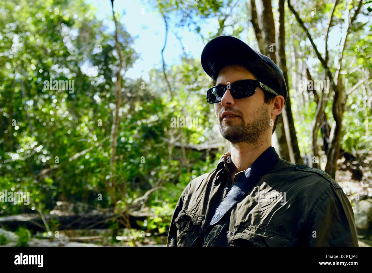 Young man wearing sunglasses and a hat in a forest, Paluma Range National Park, Rollingstone QLD, Australia - Stock Image