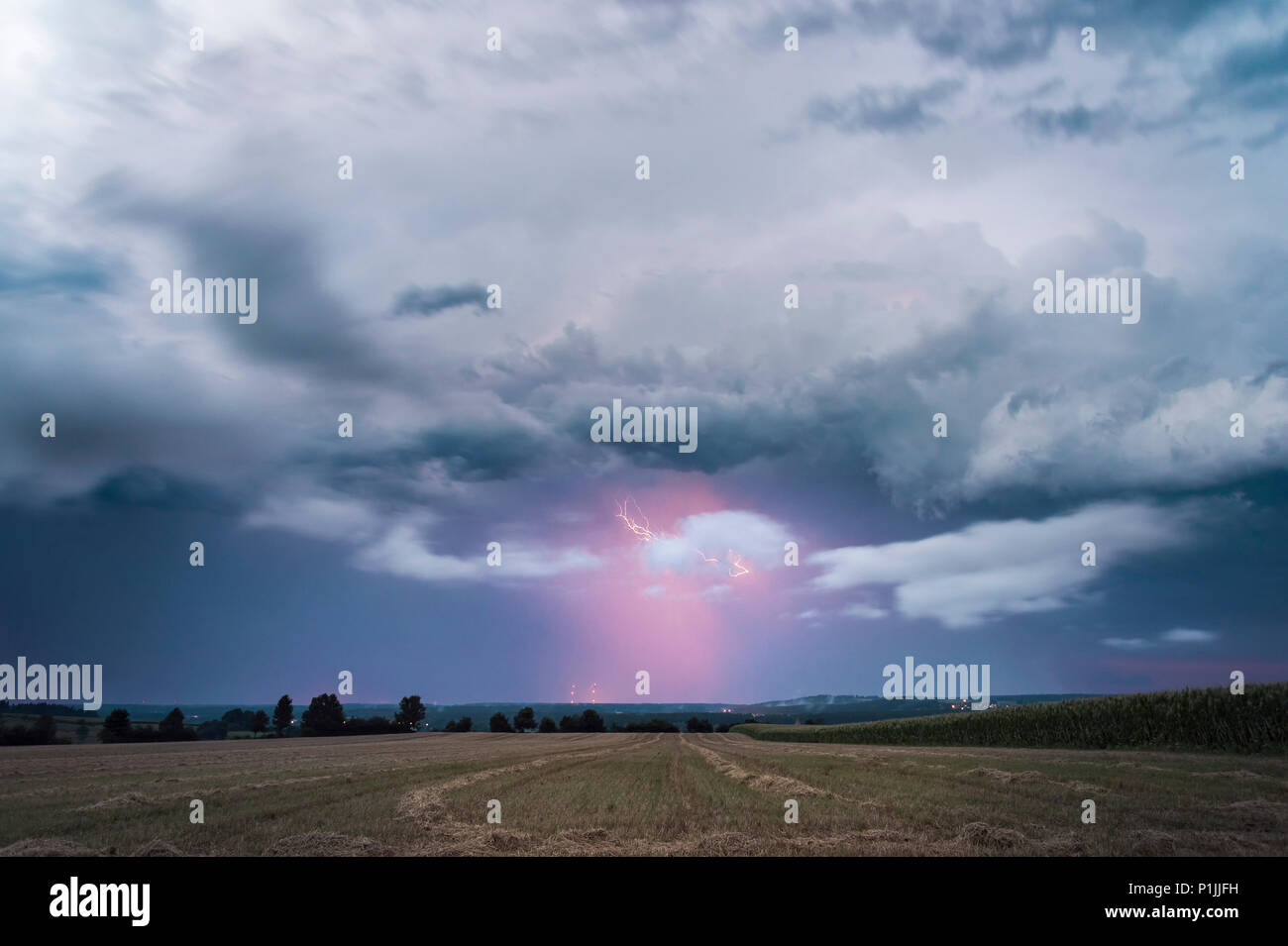 Lightning illuminated precipitation on the backside of a leaving supercell near Feuchtwangen, Baden-Wuerttemberg, Germany - Stock Image