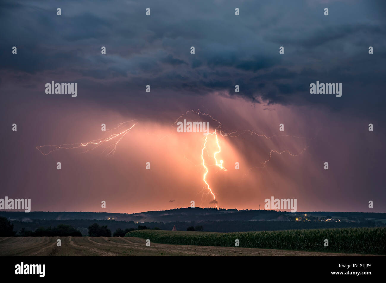 Cloud-to-ground lightning illuminated precipitation on the backside of a leaving supercell near Feuchtwangen, Baden-Wuerttemberg, Germany - Stock Image