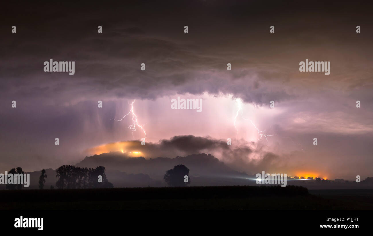 Strong cloud-to-ground lightnings behind the foggy mountain of Amöneburg, Hessia, Germany - Stock Image