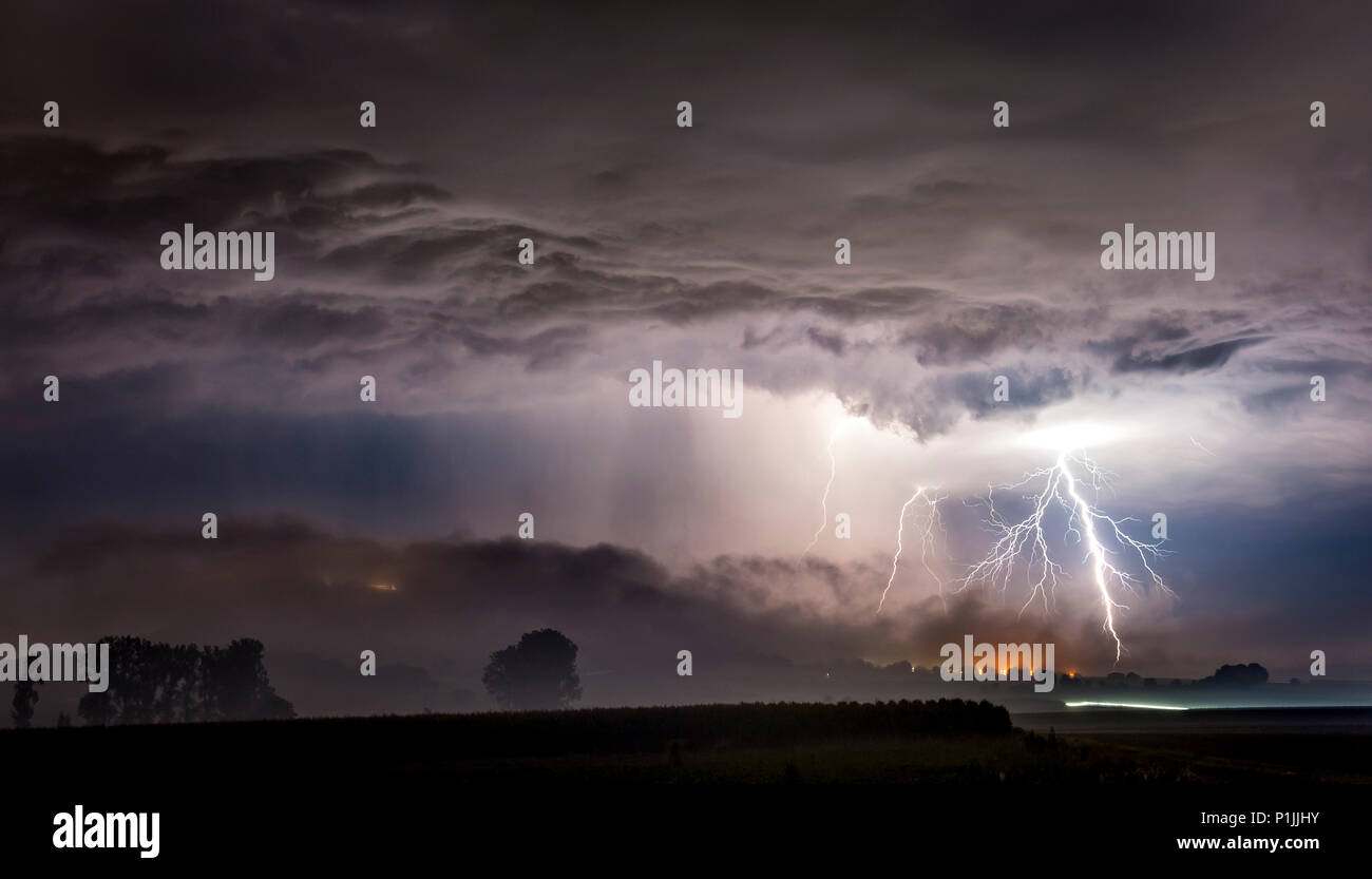 Strong branched cloud-to-ground lightnings behind the foggy mountain of Amöneburg, Hessia, Germany - Stock Image