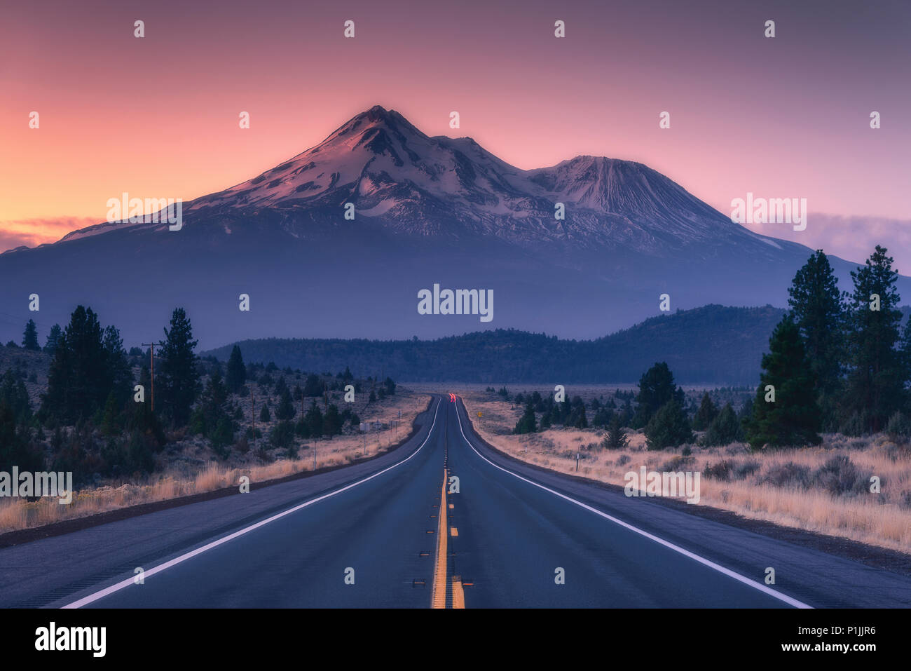Volcano Mount Shasta behind a highway during sunrise in California, USA - Stock Image