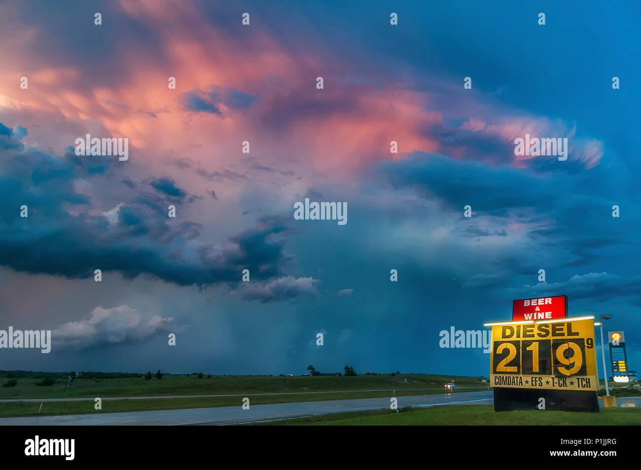 Thunderstorm (Cumulonimbus capillatus mammatus) after sunset during the blue hour with gas station in Texas, USA - Stock Image
