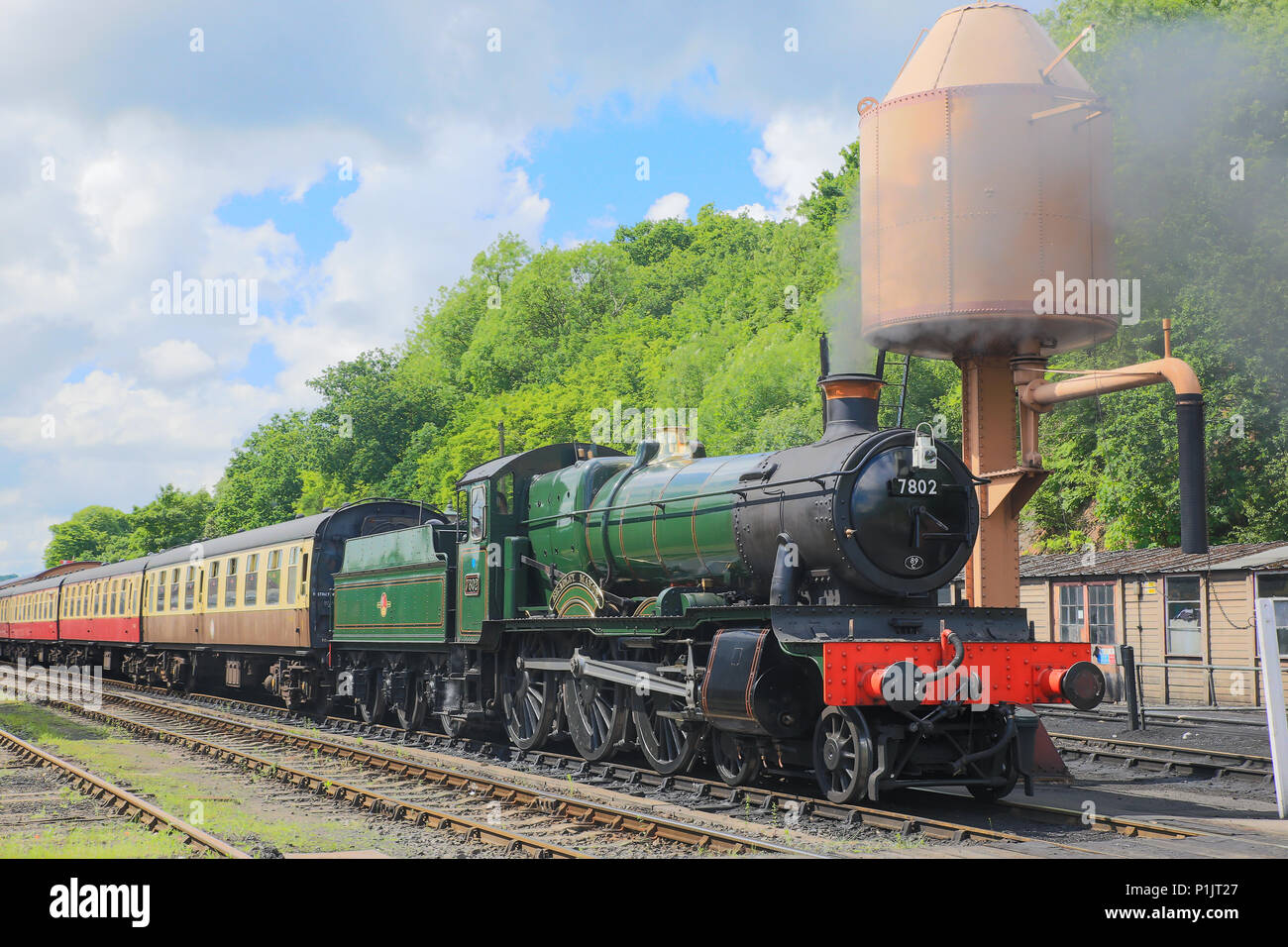 Landscape shot: puffing steam engine Bradley Manor (7802) & rake of carriages, waiting on track under water tower, southern end of SVR Bewdley station. - Stock Image