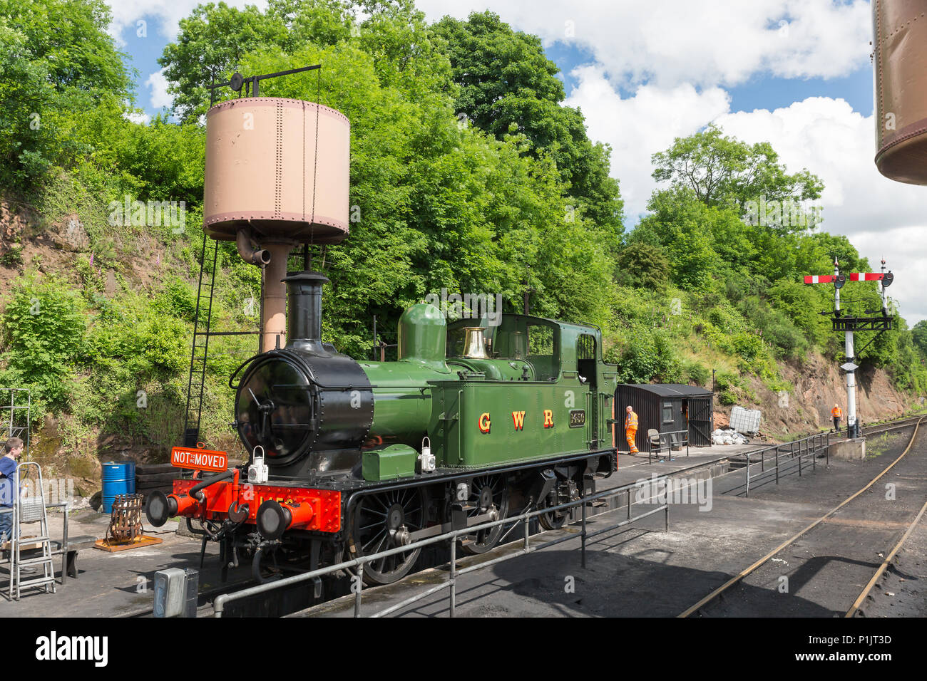 Preserved GWR steam locomotive 1450 undergoing maintenance service work, trackside at Severn Valley Railway's Bewdley station. Summer afternoon in sun. Stock Photo
