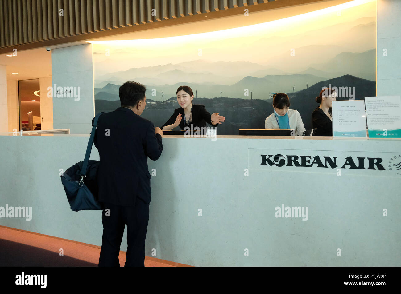A Korean Air ground staff member guides a passenger at the Miler Club Lounge at the new passenger terminal 2 of Incheon International Airport sometimes referred to as Seoul–Incheon International Airport the largest airport in South Korea located west of the city of Incheon - Stock Image