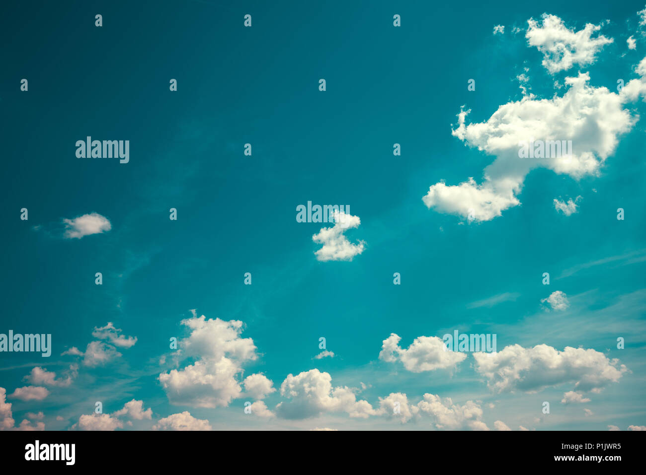 Perfect blue sky with white fluffy clouds on a sunny day. Beautiful scenic natural summertime background. - Stock Image