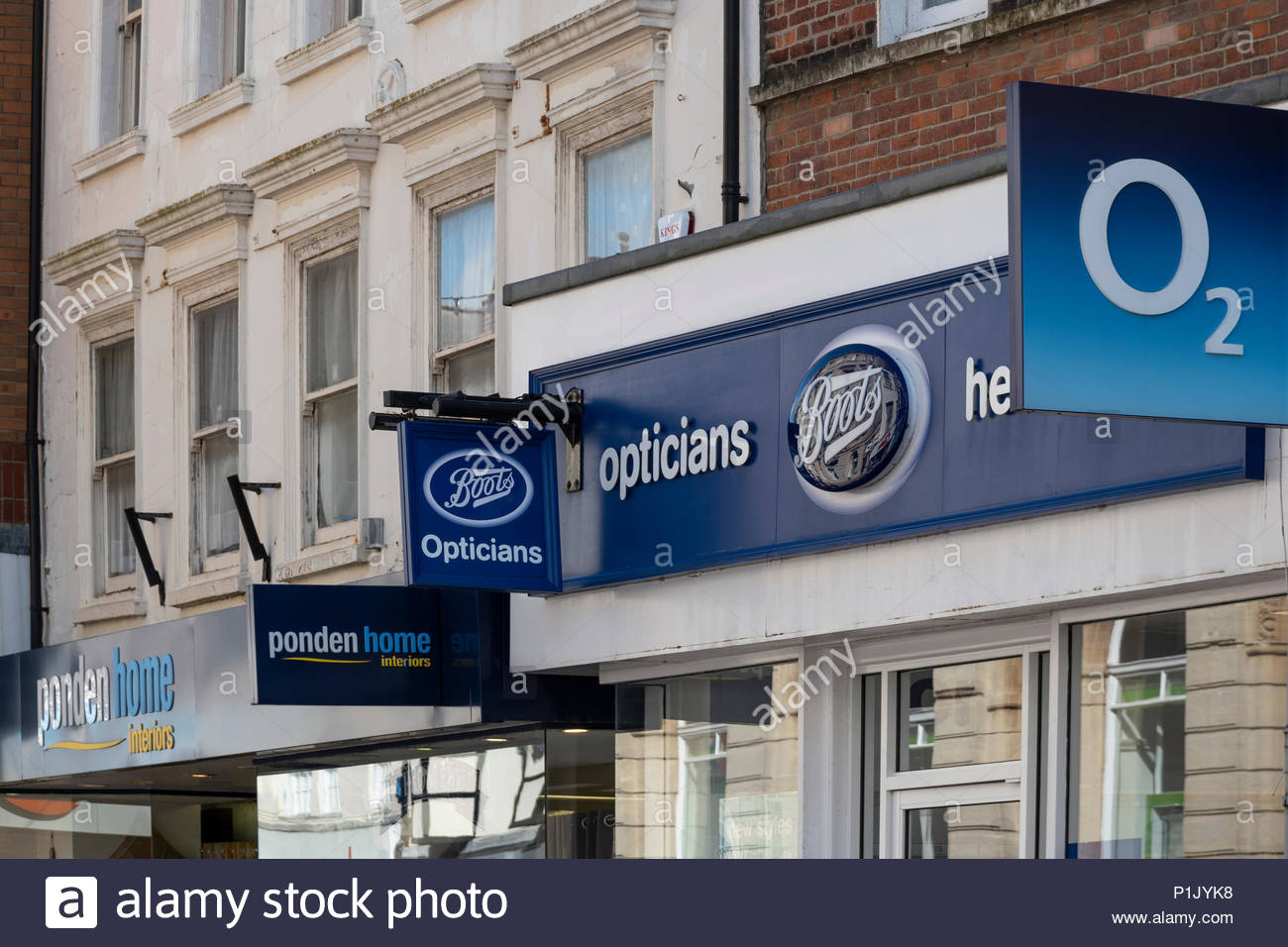 Looking up at high street shop signs including O2, Boots and Ponden Home Interiors, Weymouth, Dorset, England, UK - Stock Image
