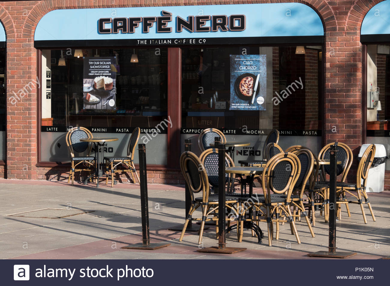 Empty table and chairs outside the Christchurch branch of Caffe Nero, Dorset, England, UK Stock Photo