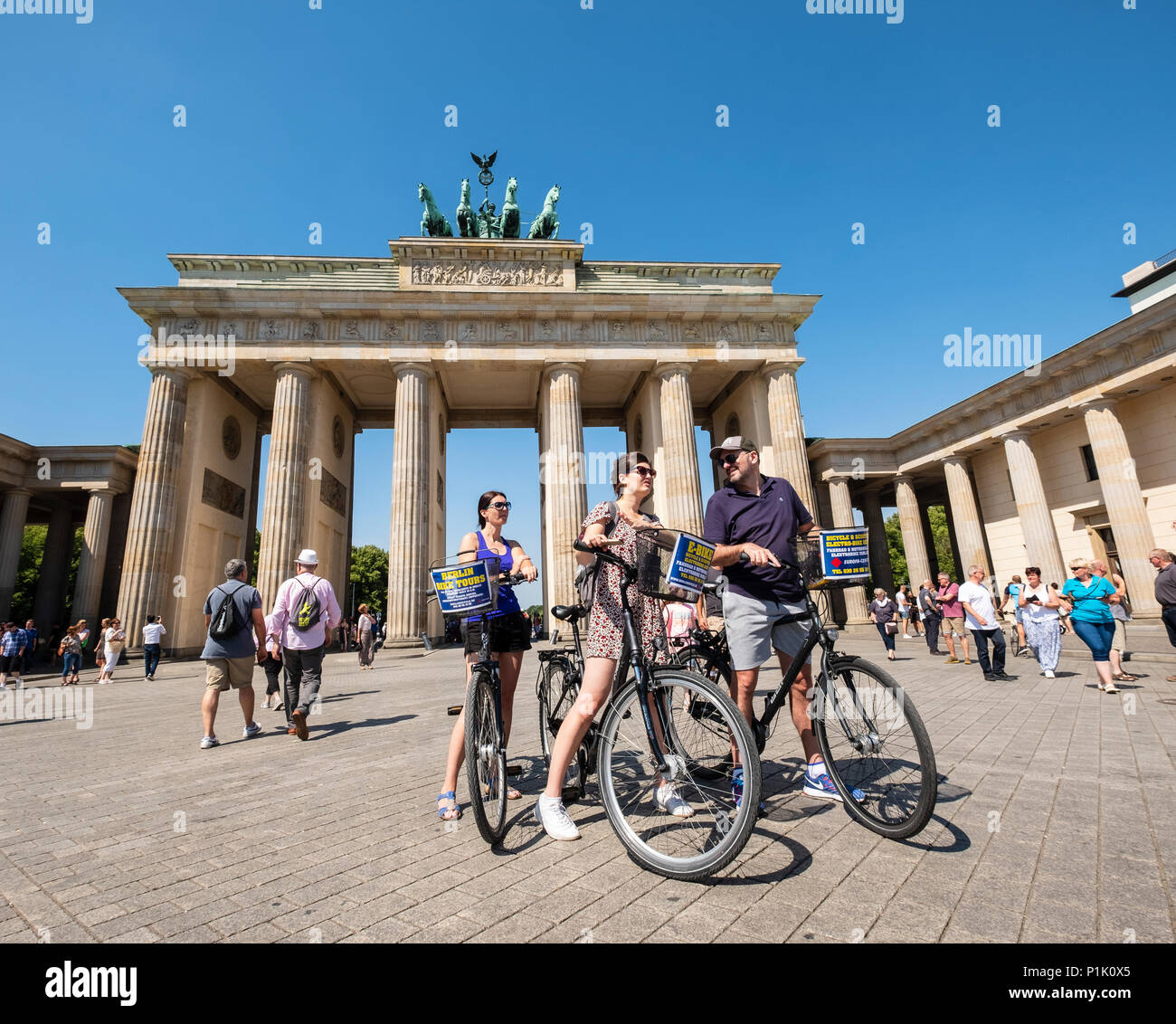 Tourists on bicycles in front of Brandenburg Gate in Berlin, Germany - Stock Image