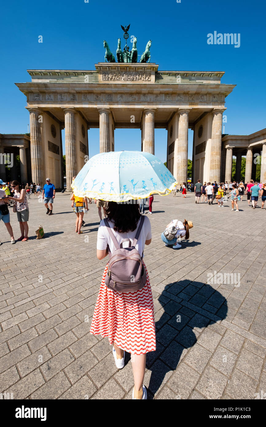 Chinese tourist with sun parasol in front of Brandenburg Gate in Berlin, Germany - Stock Image
