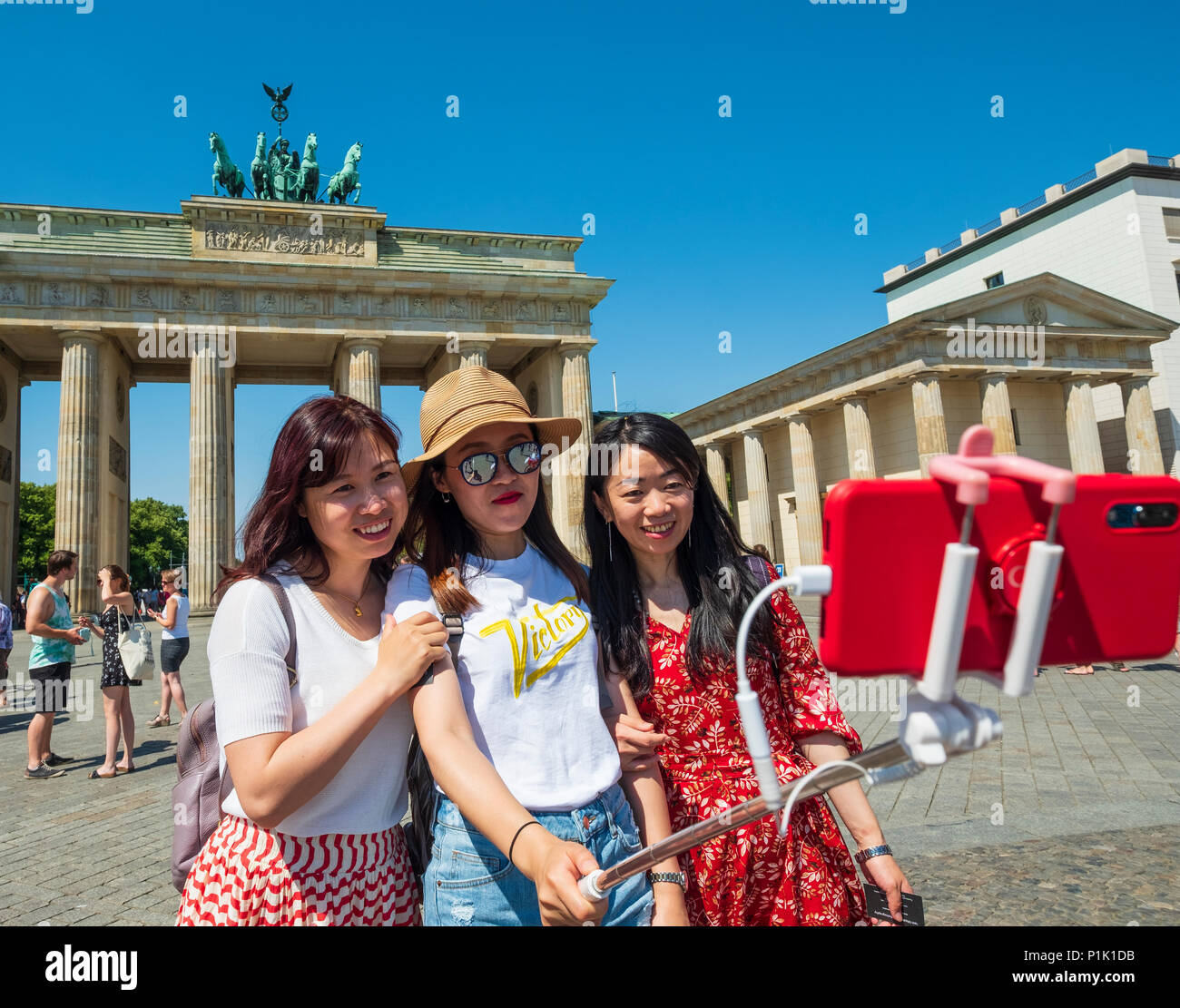 Female Chinese tourists posing with selfie stick in frontt of Brandenburg Gate in Berlin, Germany - Stock Image