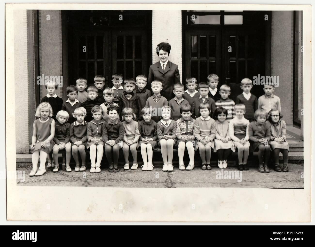 THE CZECHOSLOVAK SOCIALIST REPUBLIC - 1968: Vintage photo shows pupils (schoolmates) pose in front of school. Black & white antique photo. - Stock Image