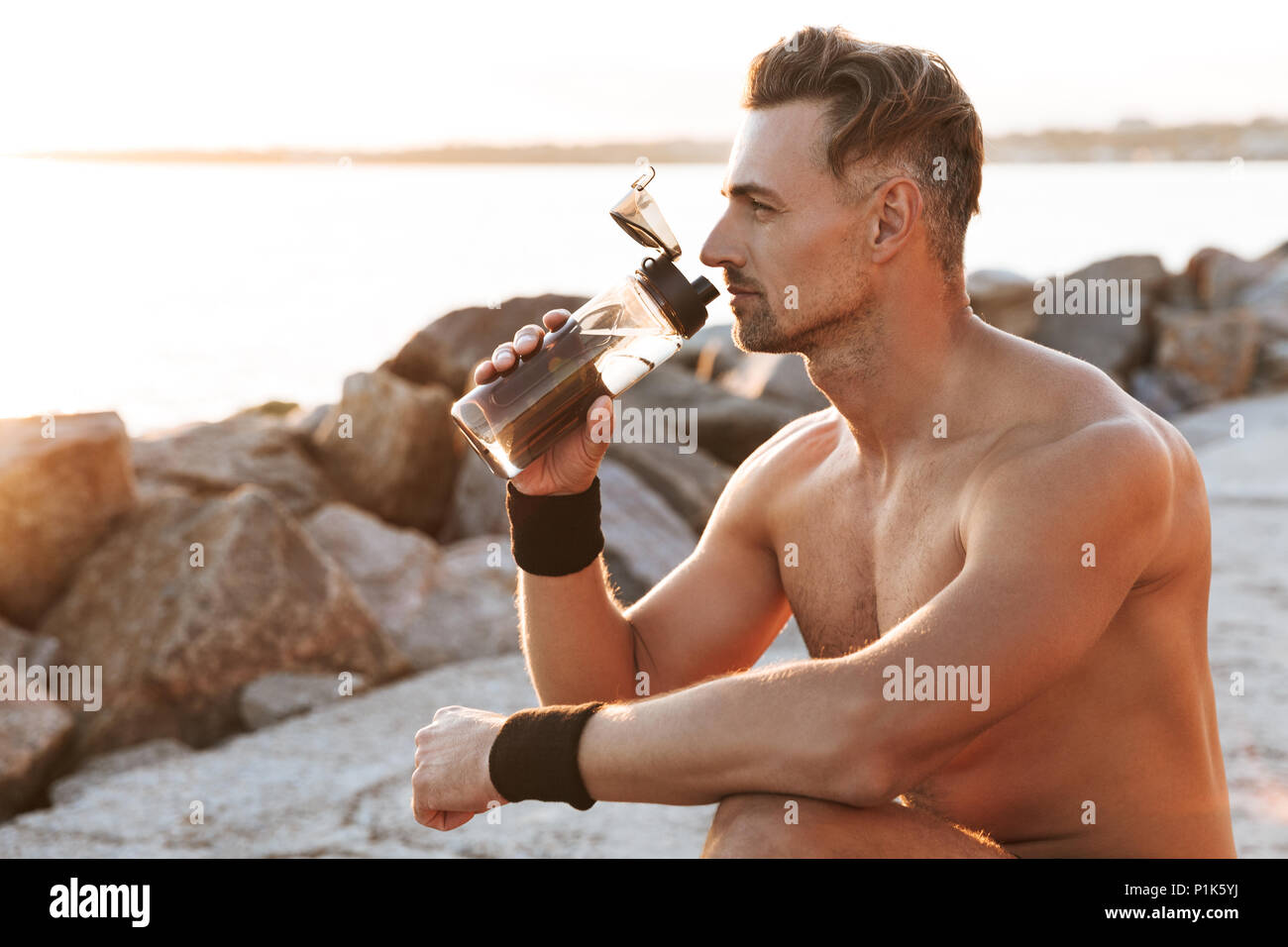 Portrait of a handsome shirtless sportsman resting after jogging and drinking water outdoors - Stock Image