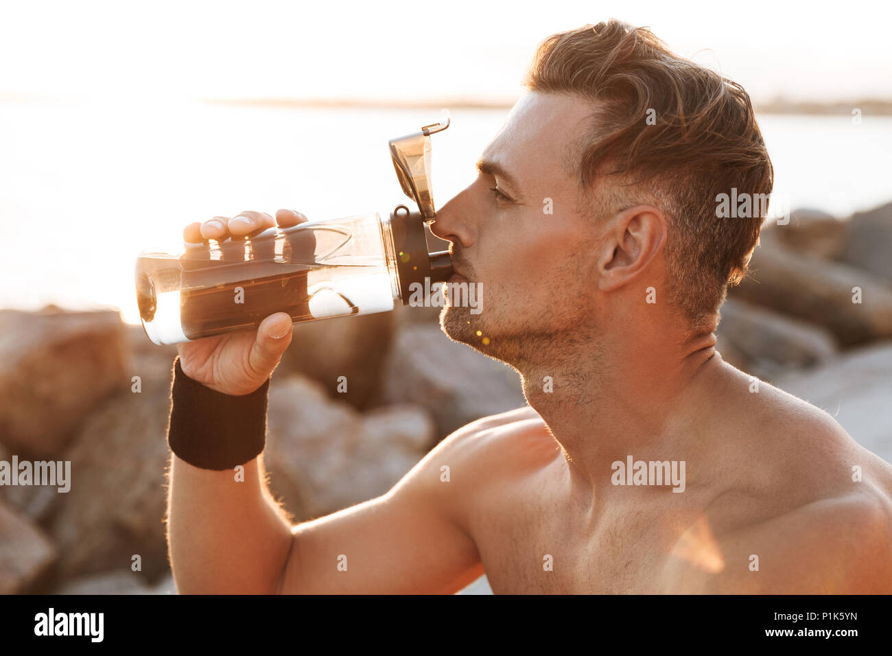 Close up portrait of a handsome shirtless sportsman resting after jogging and drinking water outdoors - Stock Image