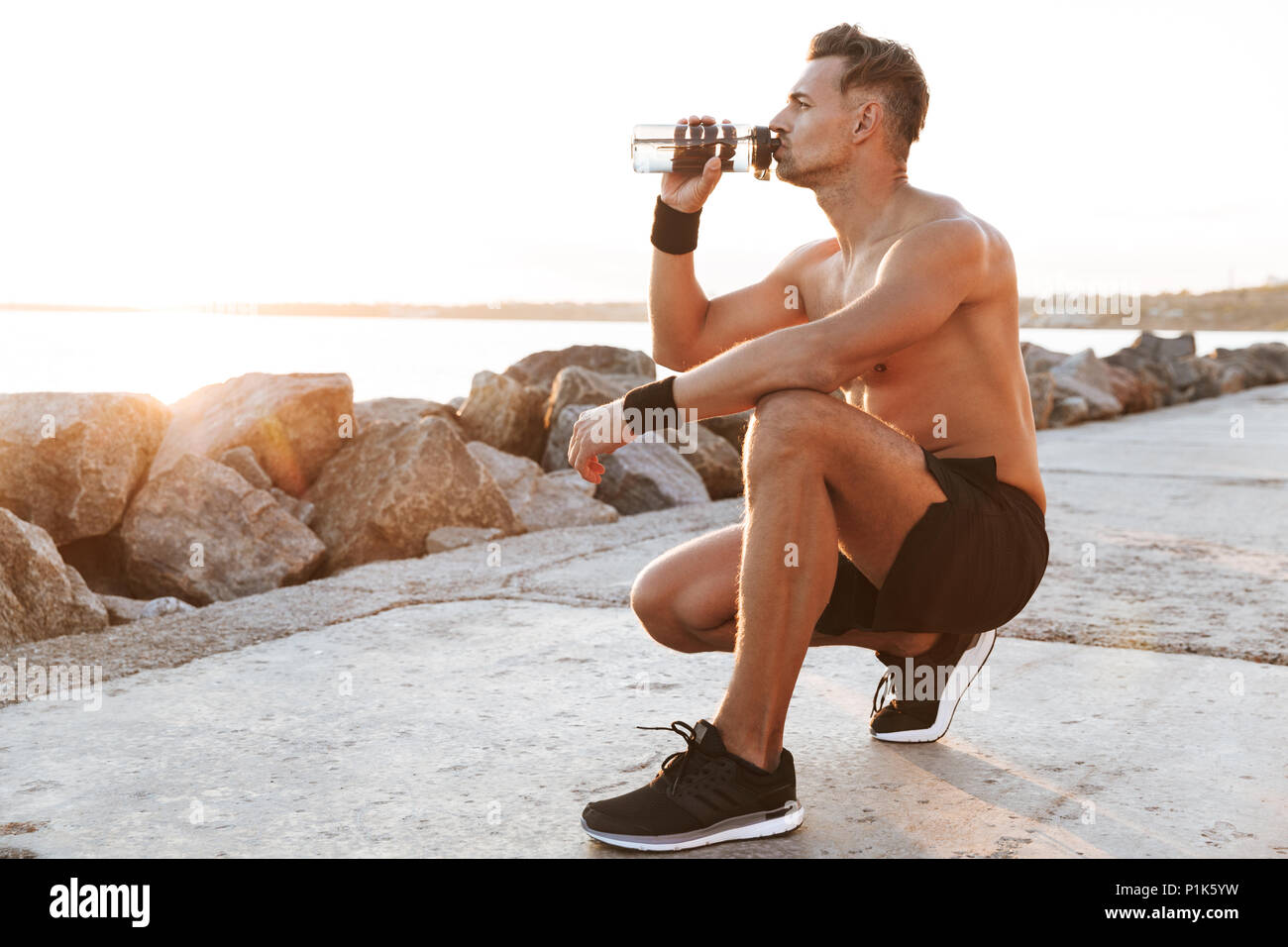 Portrait of a fit shirtless sportsman resting after jogging and drinking water outdoors - Stock Image