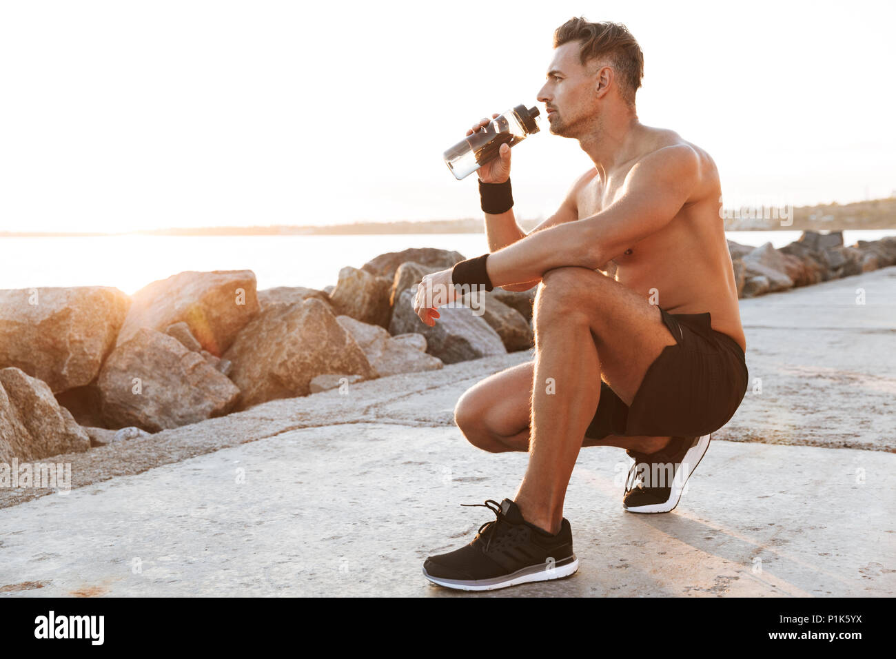 Portrait of a strong shirtless sportsman resting after jogging and drinking water outdoors - Stock Image