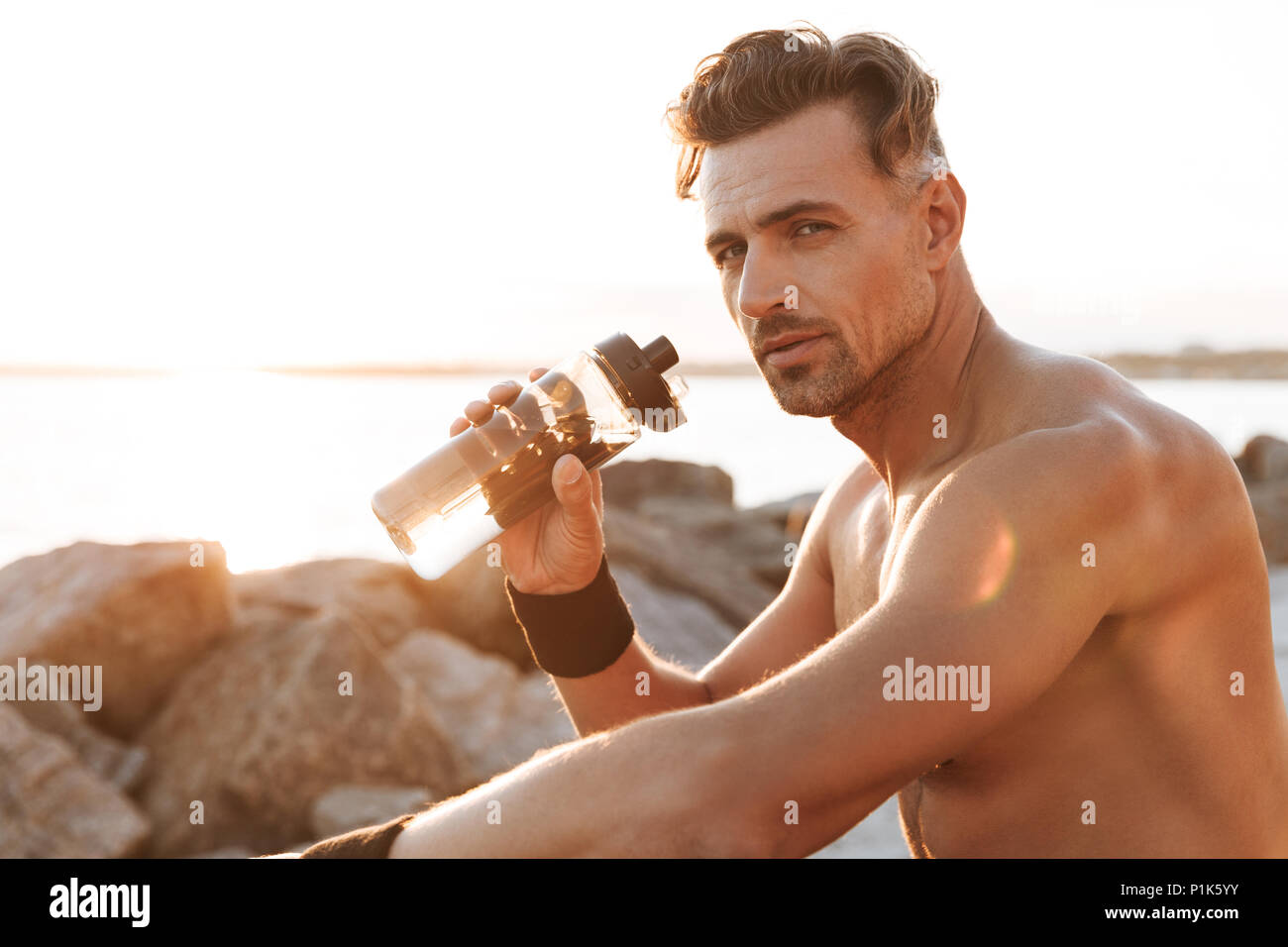Portrait of a muscular shirtless sportsman resting after jogging and drinking water outdoors - Stock Image
