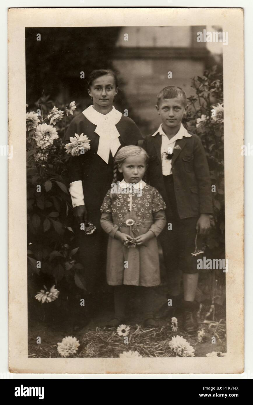 GERMANY - CIRCA 1940s: Vintage photo shows young woman with children (boy  and girl) pose in the garden. Black & white antique photography.