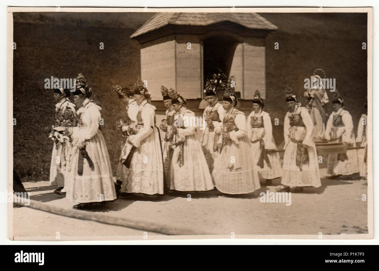 GERMANY - CIRCA 1930s: Vintage photo shows young women during religion procession. Women wear folk costums. Black & white antique photography. Stock Photo