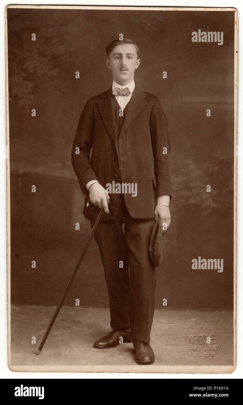 THE CZECHOSLOVAK REPUBLIC - CIRCA 1930s: Vintage photo shows a young man holds walking stick. Black & white photography with sepia effect. - Stock Image