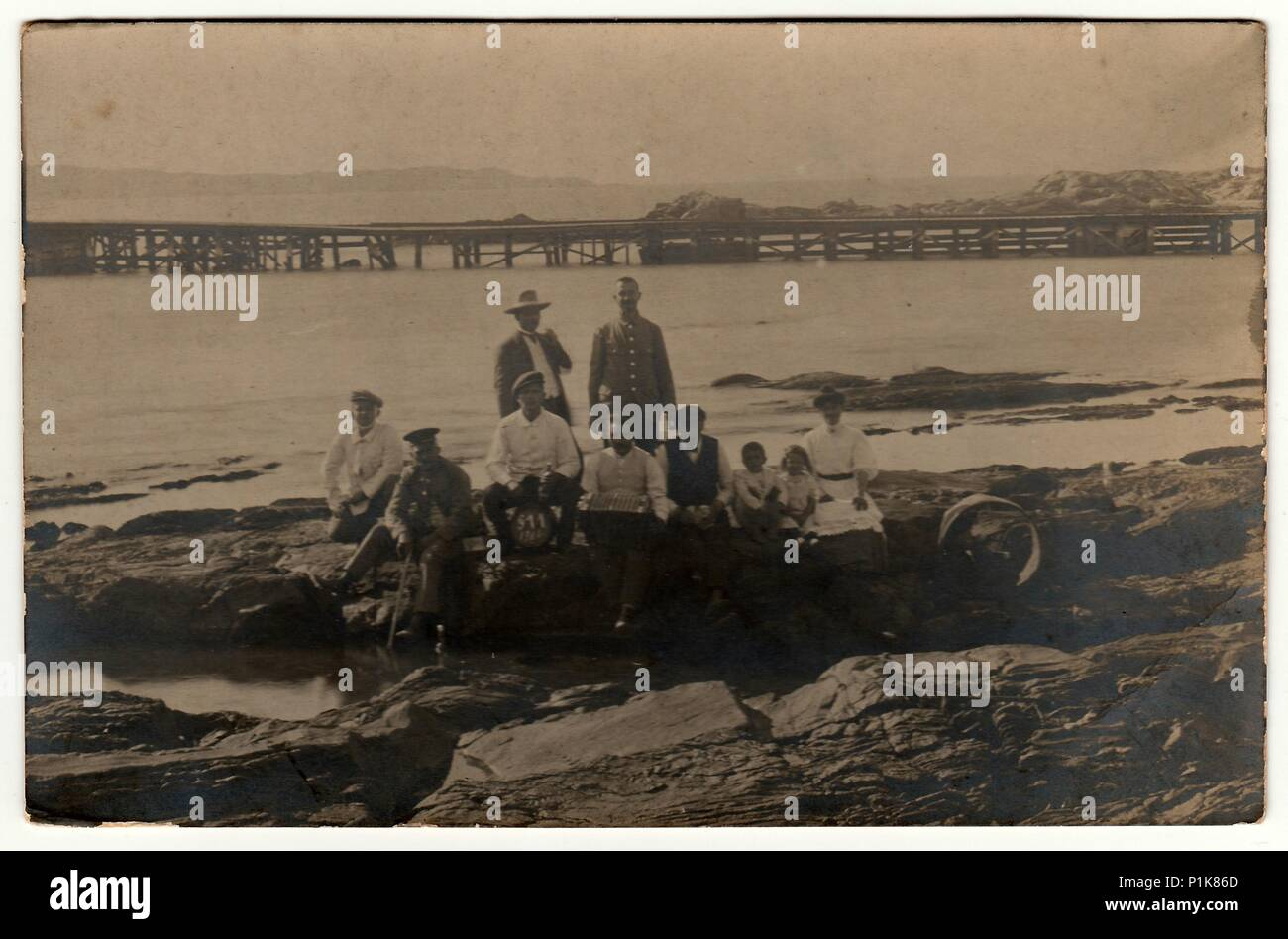 GERMANY - CIRCA 1910s: Vintage photo shows people sit at the seashore. Black & white antique photography. - Stock Image