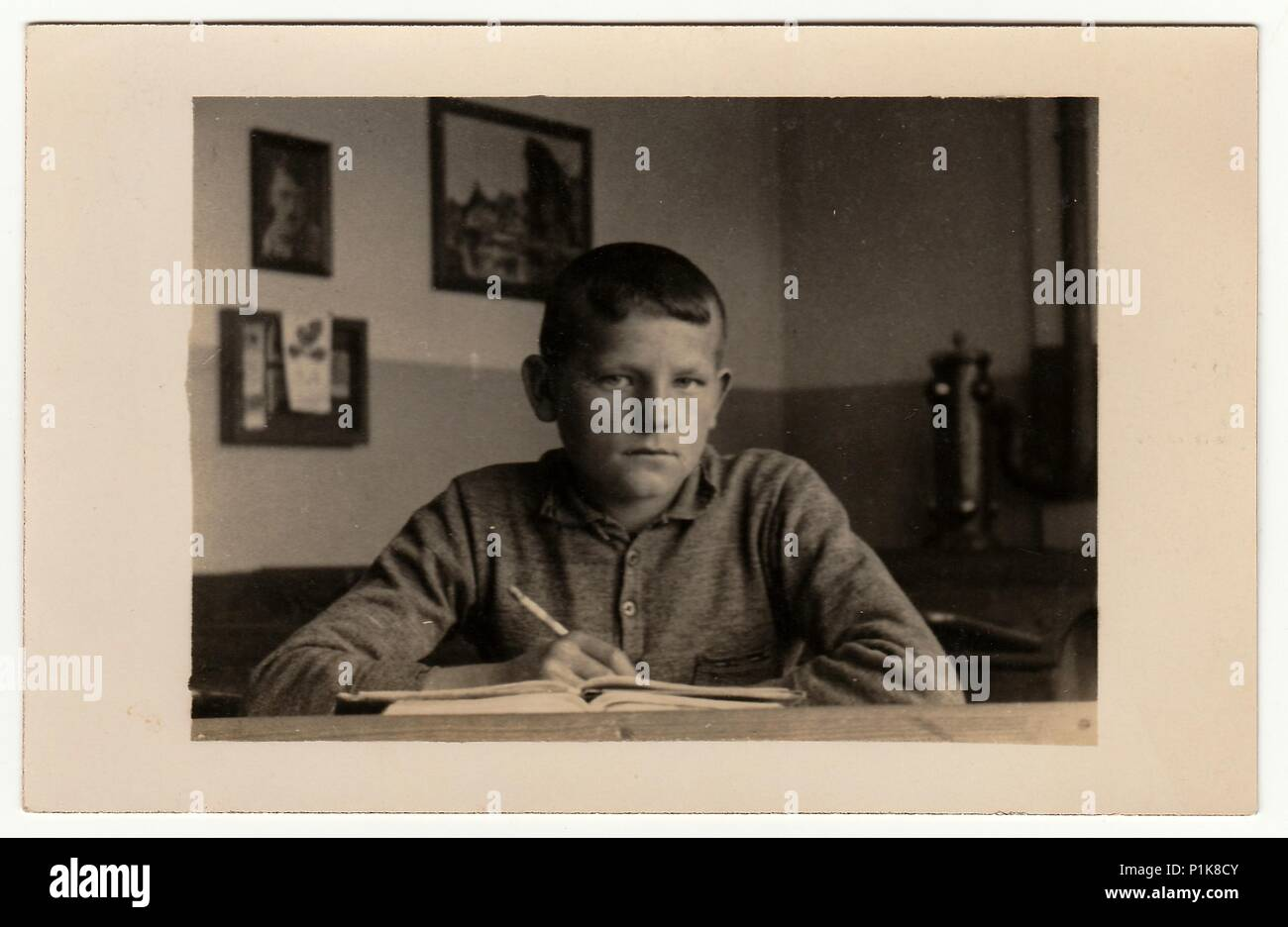 EILENBURG, GERMANY - CIRCA 1940s: Vintage photo shows young boy (pupil, student) sits at the classroom. Black & white antique photography. - Stock Image